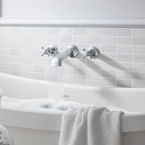 A traditional wall mounted bath spout with two crosshead handles