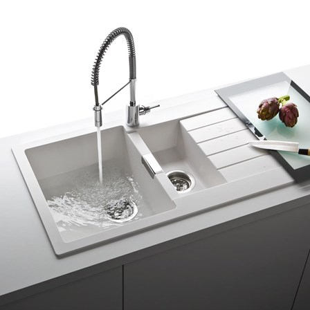 A 2 bowl white granite composite sink with a flexible tap with hose