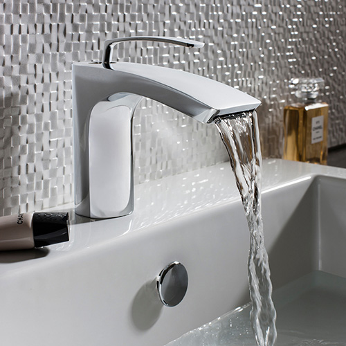 A chrome bath mono mixer monobloc over a bathtub.