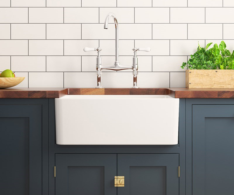 Ceramic Belfast sink on blue wooden kitchen cabinet with kitchen bridge mixer