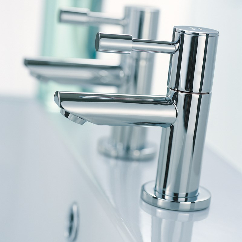 A pair of chrome basin pillar taps with a slim turn handle