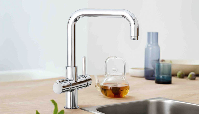 Filtered boiling water kitchen tap with a freshly brewed cup of tea