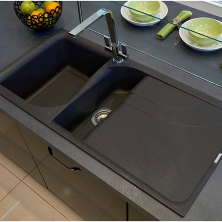 A black granite composite kitchen sink against a reflective backdrop