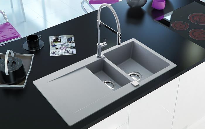A gray composite granite kitchen sink, with two bowls and a tall kitchen mixer tap in chrome.