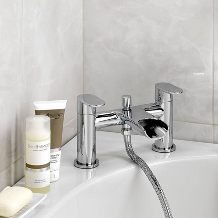 Mayfair zoe bath shower mixer situated on a bath along with some products