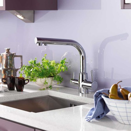 A long chrome filtered tap which is pictured against a lavender splash back.
